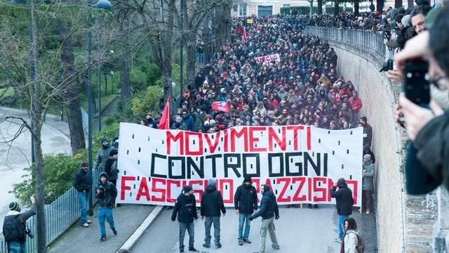 Ein Demonstrationszug hinter einem Transparent mit der Aufschrift: «Bewegung gegen jegliche Art von Faschismus und Rassismus».