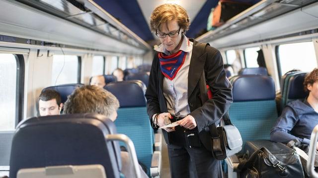 Conductura contollescha ils bigliets dals passagiers da tren.