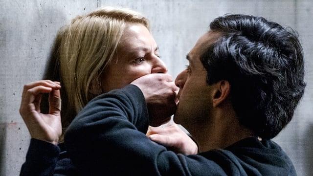 Mann hält einer Frau den Mund zu.