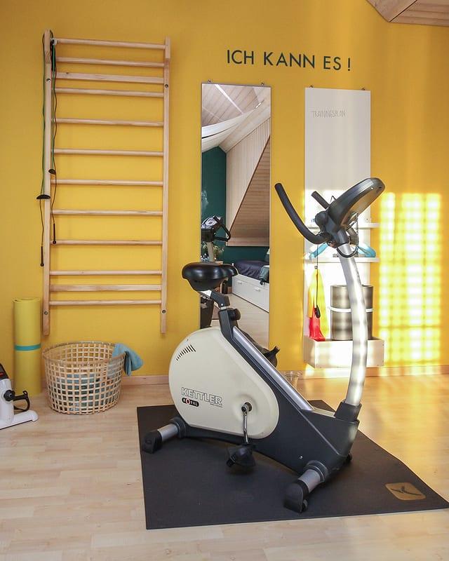 Im umgebauten Fitnessbereich konzentriert sich fast alles auf eine gelb gestrichene Wand. Daran sind eine Sprossenwand, ein Spiegel und ein Workoutboard aufgehängt. Davor steht ein Hometrainer.