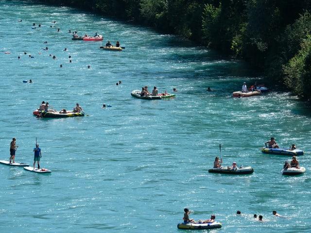 Viele Schwimmer und Boote auf einem Fluss bei heissem Wetter