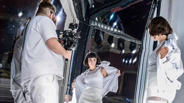 Ein Kameramann filmt eine Schauspielerin, die gerade ihre Jacke abzieht.