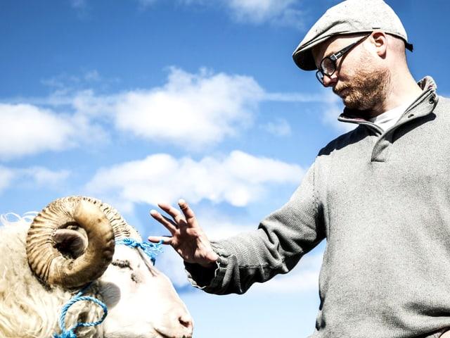 Links der Kopf eines weissen Schafbocks, rechts ein Mann, der den Bock mit der Hand beschwichtigt.