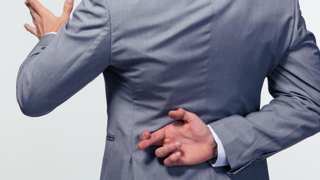 Ein Mann in Anzug spricht und überkreuzt hinter seinem Rücken die Finger.