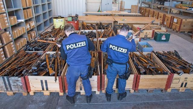 Mehrere Container mit Gewehren, davor zwei Polizisten.