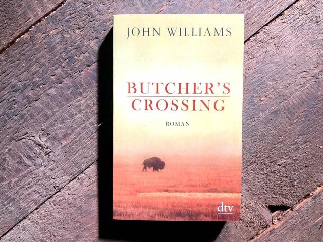 «Butcher's Crossing» von John Williams liegt auf einem dunklen Dielenboden