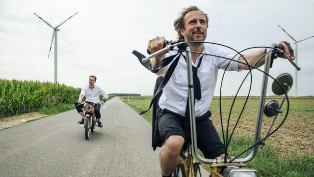Zwei Männer fahren entspannt auf alten Mofas, auf beiden Seiten der Strasse sind Felder, im Hintergrund ein Windrad.