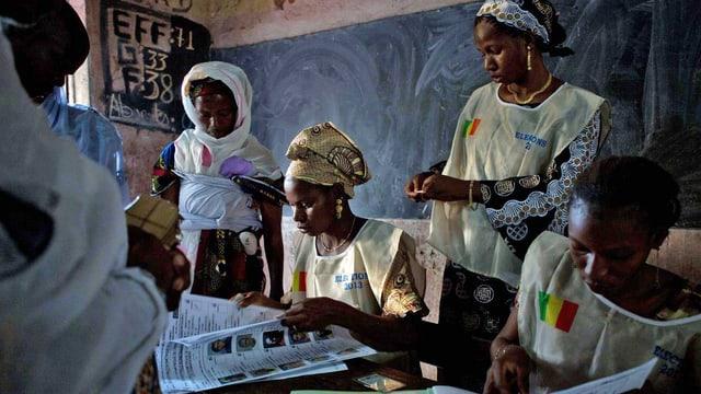 Malische Abstimmungshelferinnen nehmen Stimmzettel entgegen. In Mali findet heute die zweite Runde der Parlamentswahl statt. (keystone)