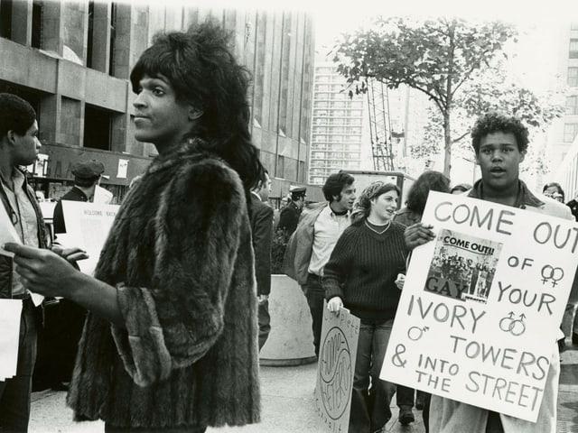 Eine schwarze Transgender-Frau verteilt Flyer an der New York University.
