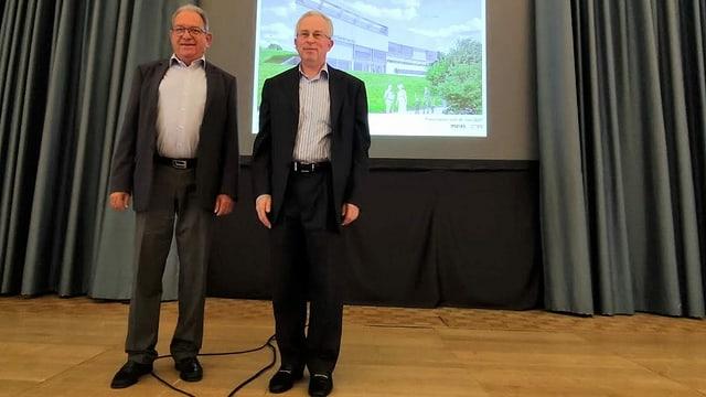 Zwei Männer im Anzug vor einer Leinwand.