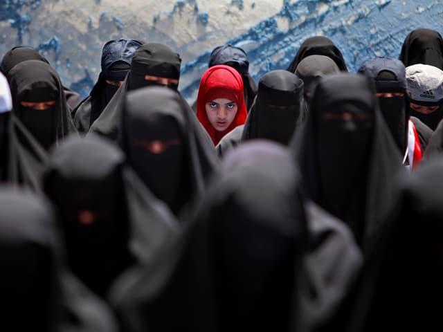 Verschleierte Frauen, in der Mitte ein Mädchen mit rotem Kopftuch.