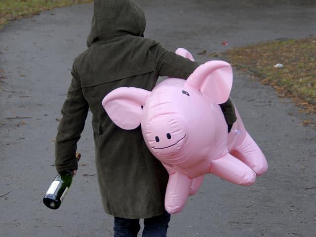 Person trägt Sektflasche und aufblasbares Plastikschwein