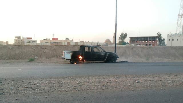 Auf einer Strasse in Tikrit steht ein ausgebranntes Auto