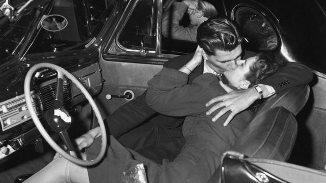 Ein altes schwarz-weiss-Foto: Eine Frau und ein Mann küssen sich in einem Auto.