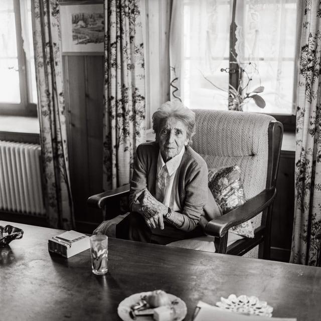 Eine alte Dame sitzt auf einem Sessel und blickt in die Kamera