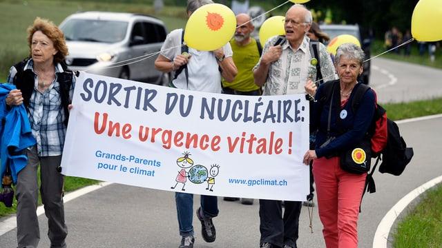Demonstrants da diversas regiuns èn sa radunads a Windisch - duas dunnas tegnan in transparent cun si: Sortir du nucléaire - une urgence vitale!