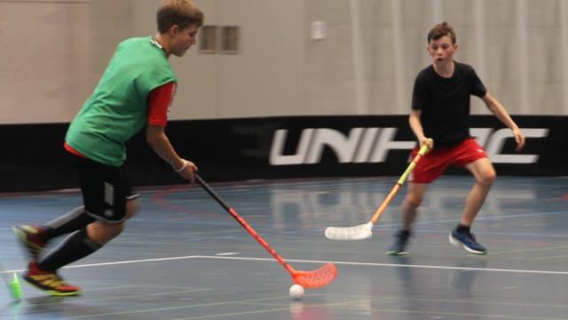 Ein Unihockey Spieler mit grünem Leibchen greift an, ein Gegner verteidigt.