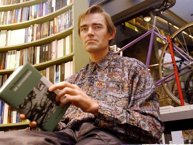Zimmermann trägt ein farbiges Hemd, und hält sein Buch in den Händen. Er sitzt in einem Zürcher Buchladen, im Schaufenster steht ein violettes Rennvelo.