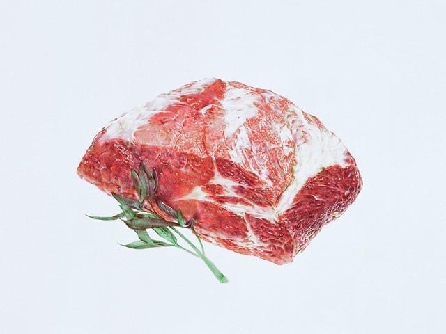 Grosses, rohes, fettdurchzogenes Stück Fleisch mit Rosmarinzweig.