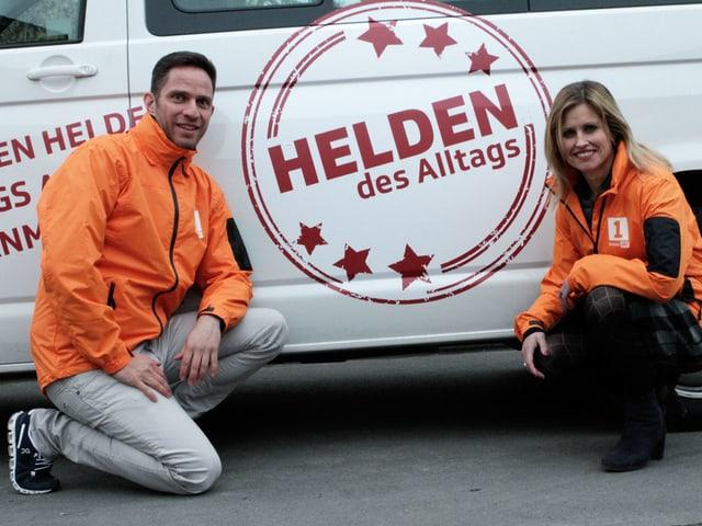 Adrian Küpfer und Sabine Dahinden knien vor dem Auto, auf dem Helden des Alltags steht.