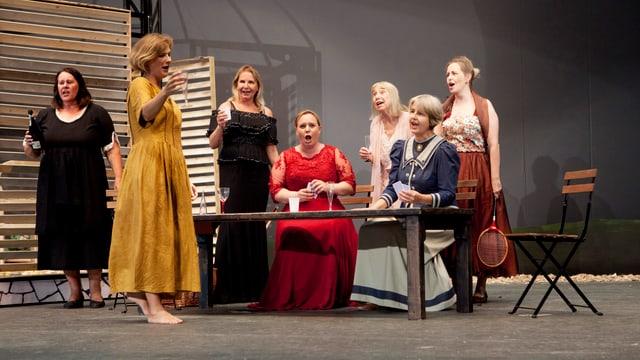 Die Kurfürstin in einer roten Robe am Singen. Sie ist umgeben von anderen Schauspielerinnen.