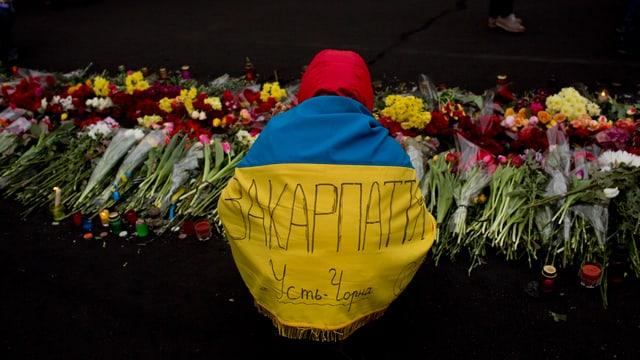 Janukowitsch-Gegner von hinten in die Fahne Ukraines eingewickelt.