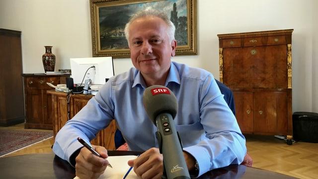 Stadtpräsident an einem Tisch mit SRF-Mikrofon.