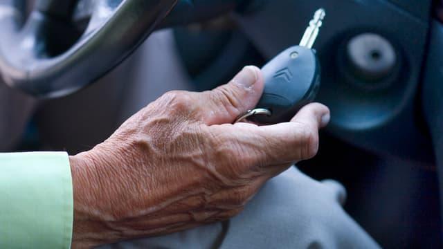 Die Hand einer älteren männlichen Person mit einem Zündschlüssel am Lenkrad.