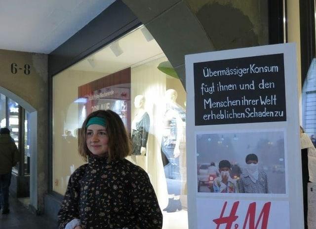 """Mädchen steht vor einem Schild mit der Aufschrift: """"Übermässiger Konsum fügt ihnen und den Menschen ihrer Welt erheblichen Schaden zu."""""""