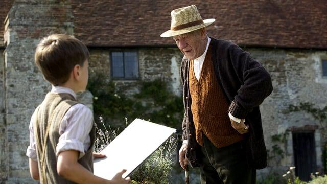 Ein älterer Mann am Stock vor einem Landhaus, vor ihm ein Junge mit einem Block.