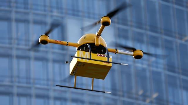 Ein beladener, gelber «Paketkopter» der Deutschen Post DHL in der Luft, dahinter ein Hochhaus mit Glasfront.