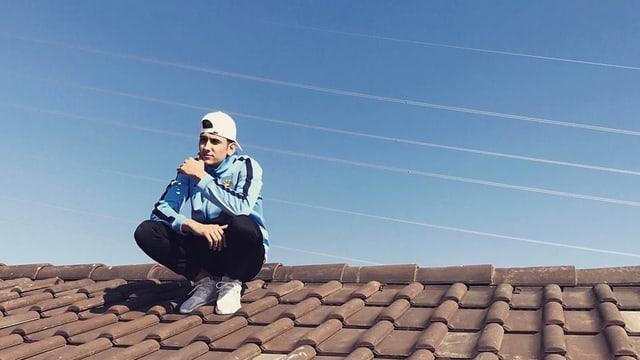 junger Rapper sitzt auf einem Dach