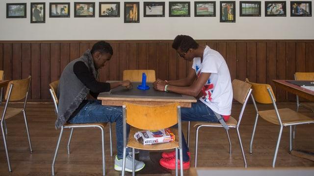 Zwei Asylbewerber sitzen an einem Tisch