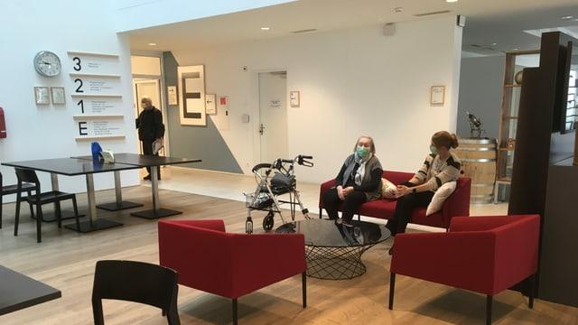 Zwei Frauen sitzen auf einem Sofa in einem Gemeinschaftsraum.