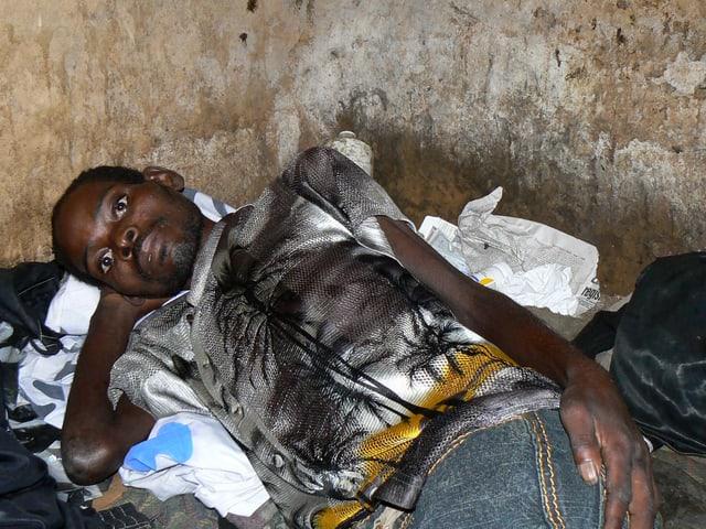 Ein schwarzer Mann liegt krank in der Ecke eines ärmlichen Hauses.