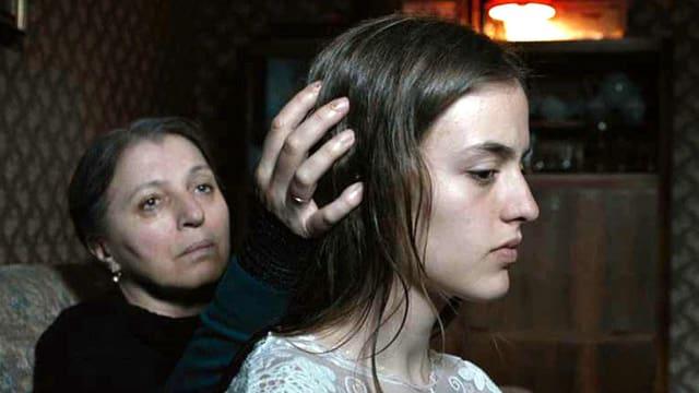 Eine ältere Frau streicht einem Mädchen mit der Hand über das Haar.
