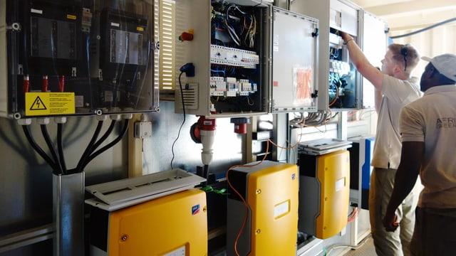 Zwei Techniker sehen in einen Stromkasten.