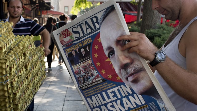 Ein Mann, rechts, liest an einer belebten Strasse eine türkische Zeitung mit Erdogan auf der Titelseite.