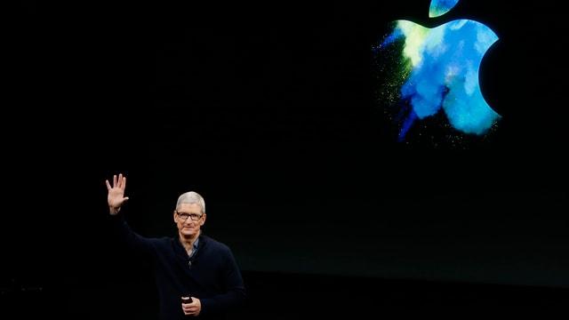 Cook vor schwarzem Hintergrund mit blauem Apple-Logo. Er winkt.