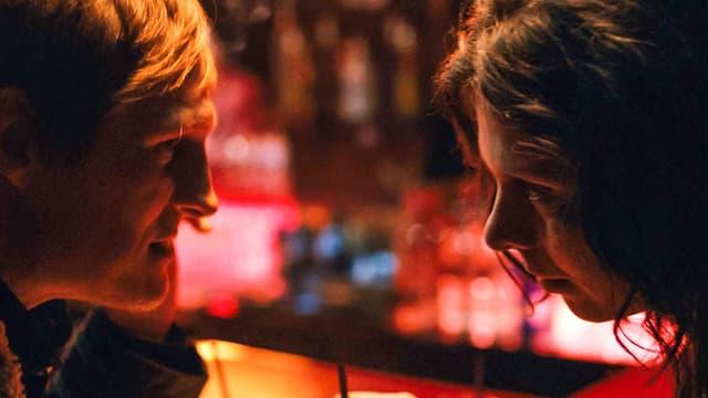 Georg (Georg Freidrich) und Marija (Margarita Breitkreiz) sitzen sich in einer Bar nahe gegenüber.