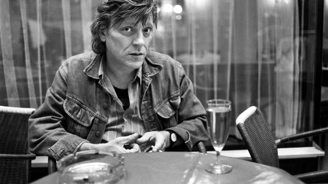 Polo Hofer sitzt an einem Tisch und raucht. Auf dem Tisch steht ein Glas. Das Foto ist schwarz-weiss. Das Foto stammt aus dem Jahr 1990.