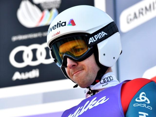 Simon Ammann mit aufgesetztem Helm und grimmiger Miene am Startbalken.
