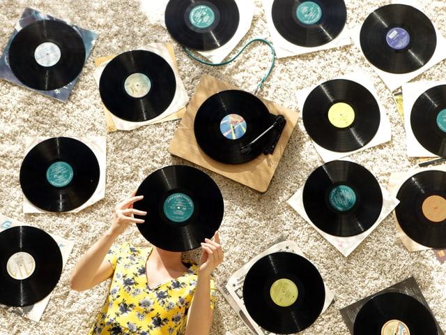 Eine Frau liegt am Boden, auf dem zahlreiche Vinyl-Platten liegen.