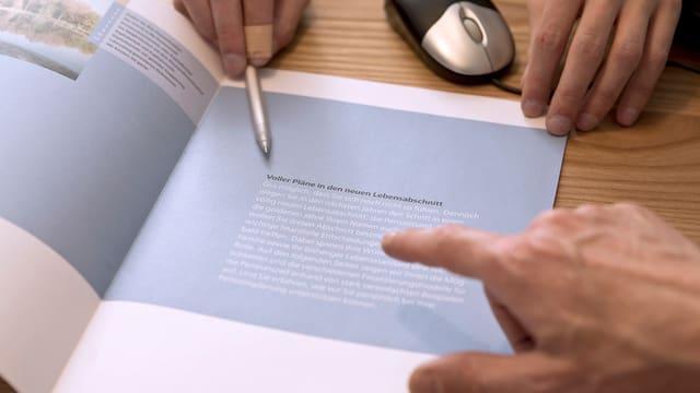 Beratungsgespräch: Jemand zeigt mit einem Kugelschreiber auf einen Prospekt, das Gegenüber hebt den Finger.