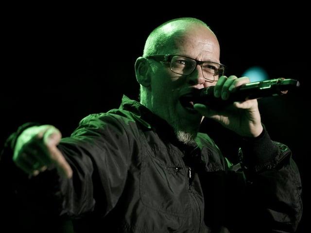 Mann Nahe mit Mikrophon am Singen, er trägt eine Sehbrille mit dunklem Rahmen