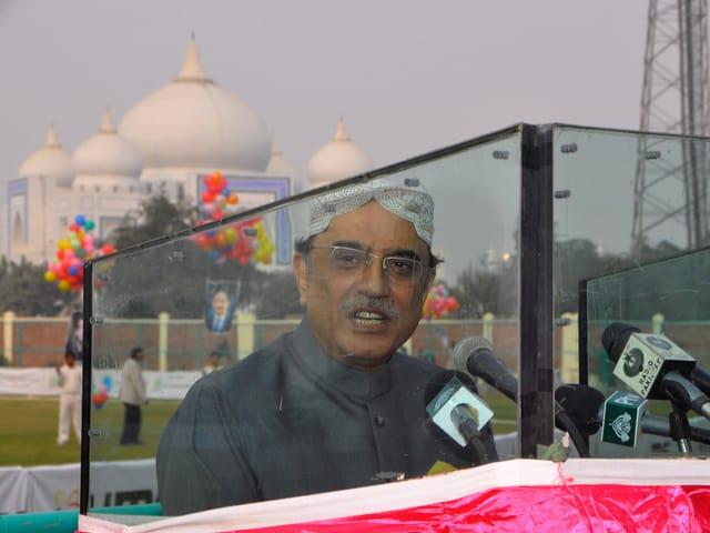 Zardari bei einer Rede hinter Panzerglas, im Hintergrund ein Mausoleum.