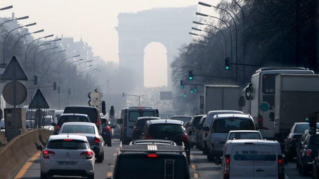 Fahrzeuge auf einer Strasse im Hintergrund ein Triumphbogen.