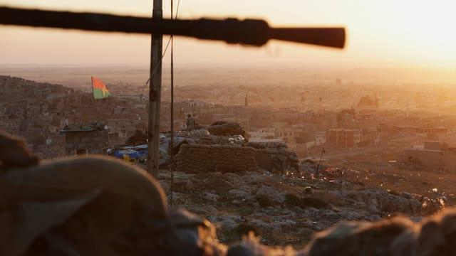 Symbolbild: Ein Gewehrror und ein Panzer, im Hintergrund eine Wüstenstadt.