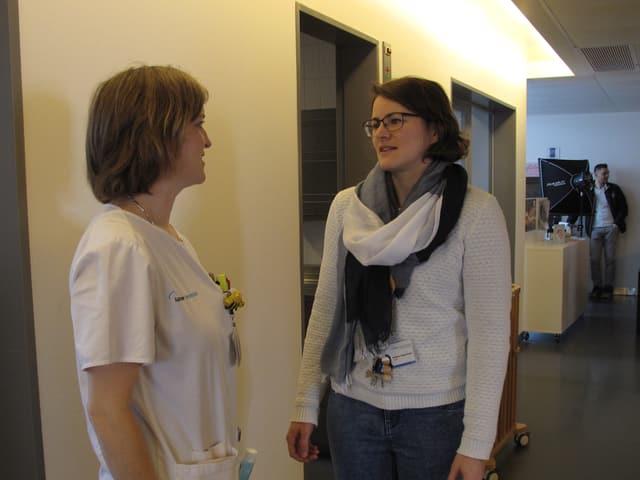 Zwei junge Frauen, die in einem Flur miteinander sprechen.