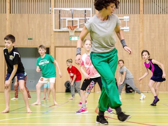 Turnhalle, Lucia Baumgartner tanzt vor, im Hintergrund Kinder, die nachtanzen